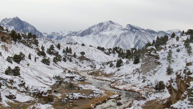 aerial shot of tourists at creek amidst snow against sky, drone descending forward towards hot creek geological site against snowcapped mountains - mammoth lakes, california - mammoth lakes video stock e b–roll