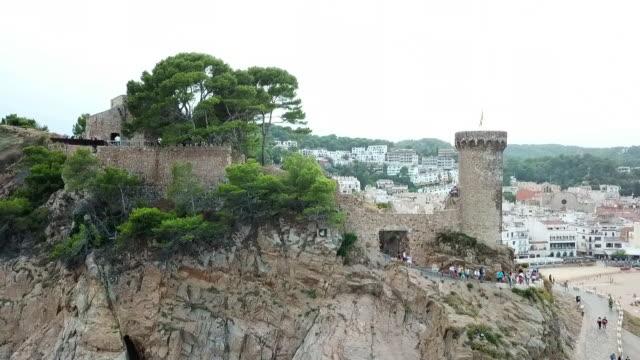 vidéos et rushes de aerial shot of tourists at famous castle at beach, drone ascending backward from historic landmark by city against sky - tossa de mar, spain - mar