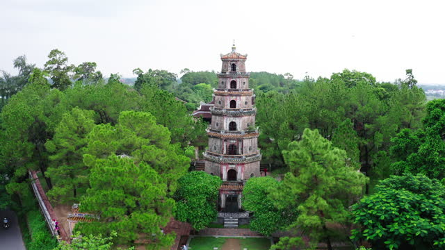 aerial shot of tourists at famous thien mu pagoda against sky, drone flying forward towards popular landmark amidst green trees - hue, vietnam - pagoda stock videos & royalty-free footage