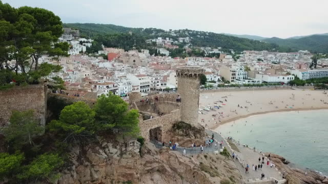 aerial shot of tourists at historic fort on rock formation, drone flying backward from city against sky - tossa de mar, spain - fortress stock videos & royalty-free footage
