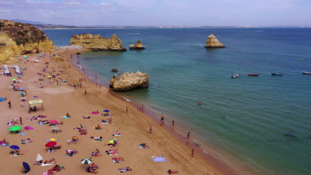 aerial shot of tourists enjoying at beach by cliffs on sunny day, drone flying forward towards sea against sky - lagos, portugal - portugal stock videos & royalty-free footage