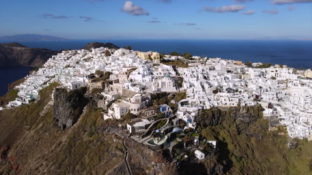 aerial shot of tourists exploring whitewashed city, drone ascending backward from white structures against sky on sunny day - santorini, greece - cyclades islands stock videos & royalty-free footage