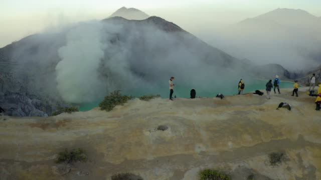 aerial shot of tourists on rocky mountain peak by lake and smoke, drone flying forward over people - east java, indonesia - sulphur stock videos & royalty-free footage