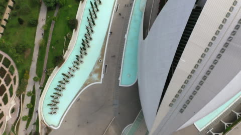 aerial shot of tourists walking on footpath by modern building, drone flying forward over famous landmark in city - valencia, spain - footpath stock videos & royalty-free footage