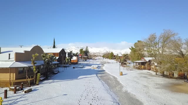 aerial shot of town covered with snow against blue sky, drone flying forward over road on sunny day - joshua tree, california - joshua tree national park stock videos & royalty-free footage