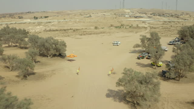 aerial shot of tracks amidst trees near road at desert, drone descending forward towards shade and vehicles - negev, israel - negev stock videos & royalty-free footage
