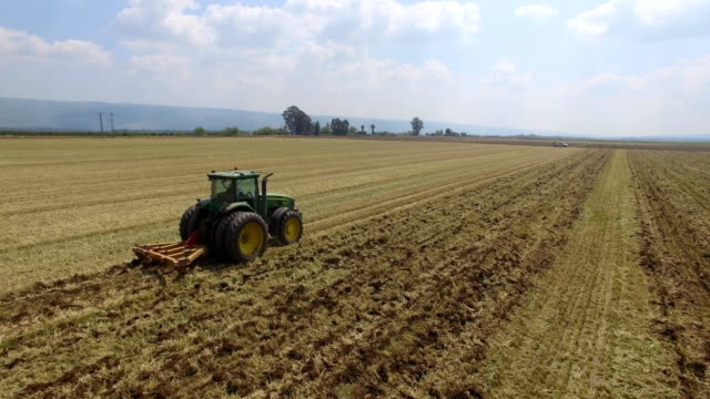 aerial shot of tractor ploughing dry field in the hula valley - pflug stock-videos und b-roll-filmmaterial