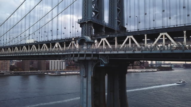 vídeos de stock, filmes e b-roll de aerial shot of traffic and subway trains passing over new york's manhattan bridge on a cloudy fall morning. - manhattan bridge
