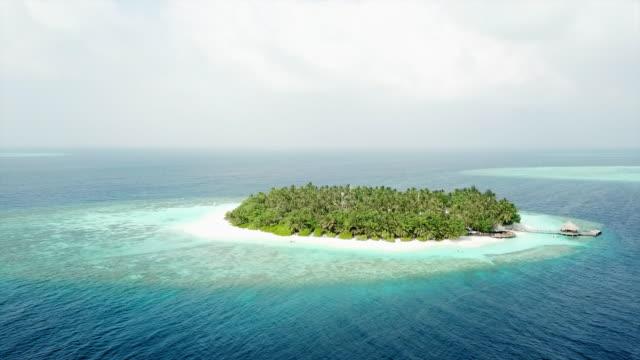 stockvideo's en b-roll-footage met aerial shot of tropical island and surrounding ocean - vabbinfaru, maldives - omgeven