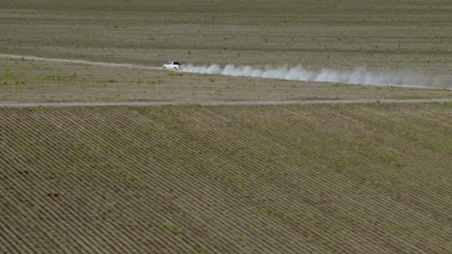 vídeos de stock e filmes b-roll de aerial shot of truck driving on dirt road - pick up