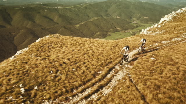 aerial shot of two mountain bikers riding the ridge - mountain bike stock videos & royalty-free footage