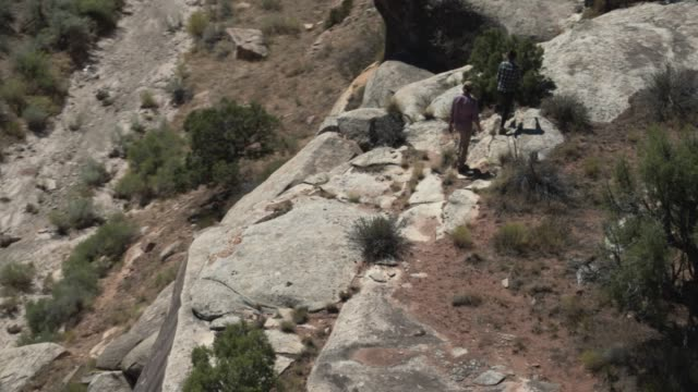 luftaufnahme von zwei menschen zu fuß auf einem felsigen rand des colorado national monument in der wüste von grand junction, colorado - felswand stock-videos und b-roll-filmmaterial