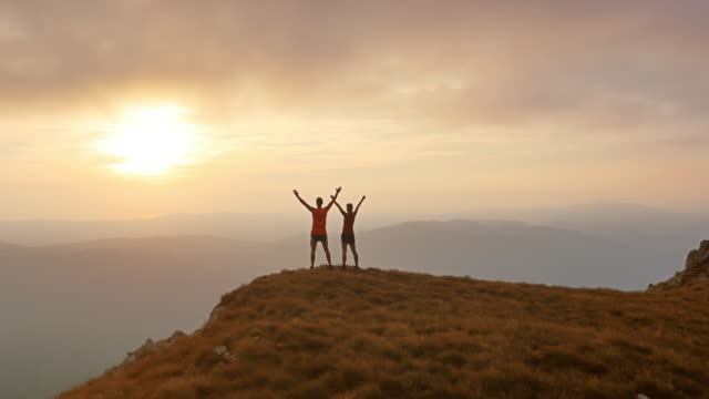 aerial shot of two runners reaching the top at sunset - on top of stock videos & royalty-free footage