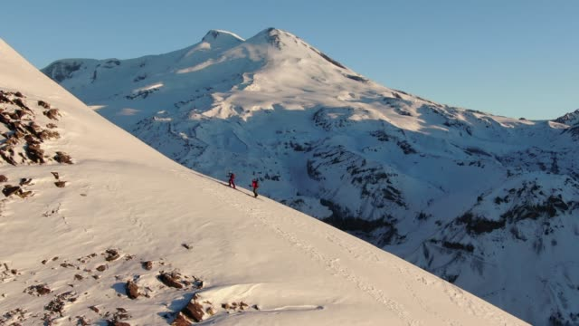 aerial shot of two skiers hiking up a mountainside - skiing stock videos & royalty-free footage