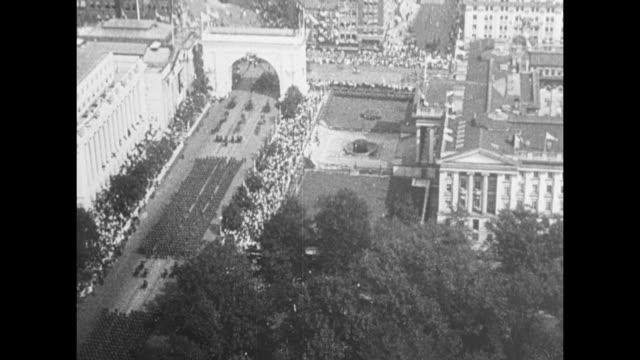 aerial shot of us military horsedrawn wagons rolling down street crowds on either side / aerial shot of washington square park and its arch /... - 凱旋門点の映像素材/bロール