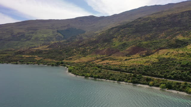 vidéos et rushes de aerial shot of vehicle on road amidst green plants by lake, drone flying forward towards mountain range on sunny day - queenstown, new zealand - nouvelle zélande
