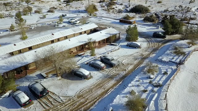 aerial shot of vehicles in snow covered town on sunny day, drone flying forward over wooden structures - joshua tree, california - joshua tree national park stock videos & royalty-free footage