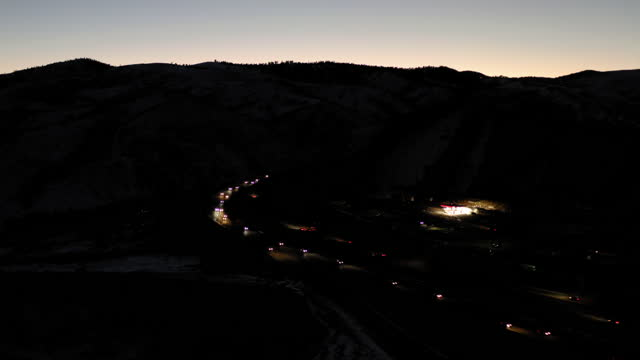 aerial shot of vehicles moving on highway amidst foothills at dusk, drone over landscape in winter - denver, colorado - denver stock videos & royalty-free footage