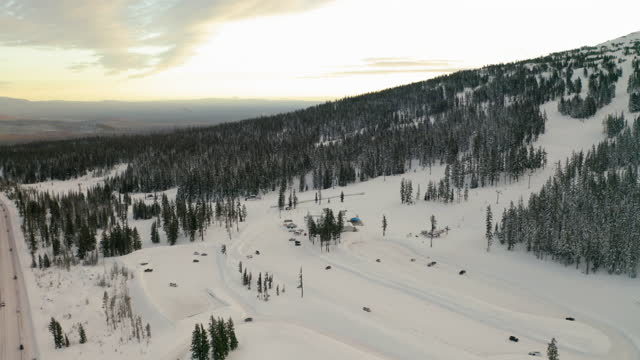 aerial shot of vehicles moving over snow covered landscape, drone flying over forest - bend, oregon - ski resort stock videos & royalty-free footage