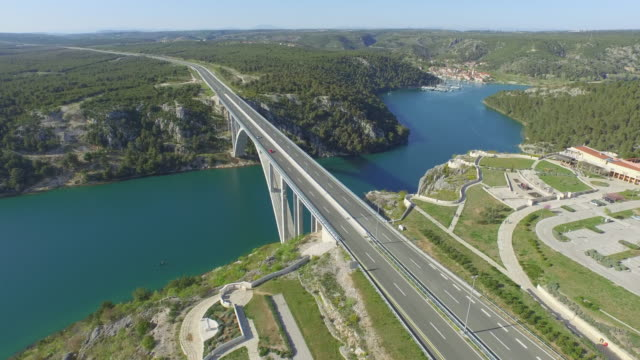 aerial shot of vehicles on famous arch bridge over river, drone flying forward over road against sky on sunny day - heart island, croatia - arch bridge stock videos & royalty-free footage
