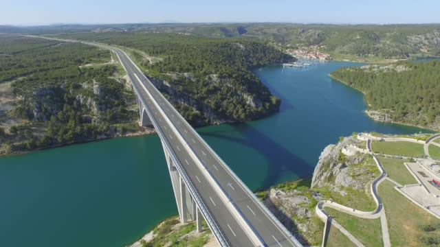 aerial shot of vehicles on famous arch bridge over river near town, drone flying forward over road against sky on sunny day - heart island, croatia - arch bridge stock videos & royalty-free footage