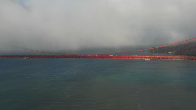aerial shot of vehicles on famous golden gate bridge under fog over bay, drone flying over sea with popular landmark bridge - san francisco, california - 水の形態点の映像素材/bロール