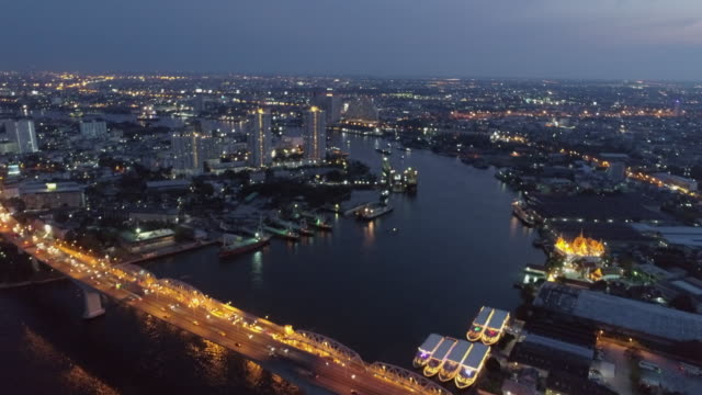 aerial shot of vehicles on illuminated bridge over river in city at night, drone flying forward over cityscape against sky - bangkok, thailand - 行く手点の映像素材/bロール