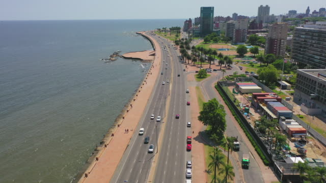aerial shot of vehicles on road amidst sea and buildings in city, drone flying forward over street on sunny day - montevideo, uruguay - montevideo stock-videos und b-roll-filmmaterial
