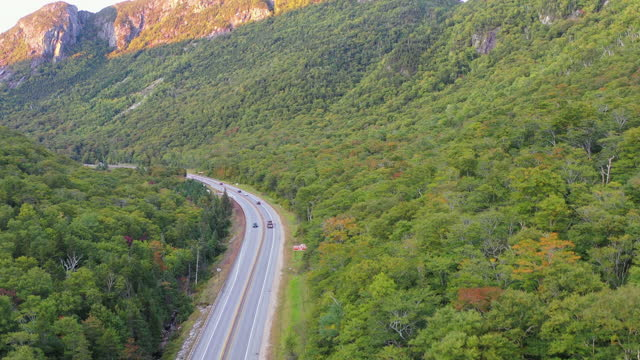 stockvideo's en b-roll-footage met aerial shot of vehicles on road amidst trees at mountain during autumn - franconia, new hampshire - new hampshire