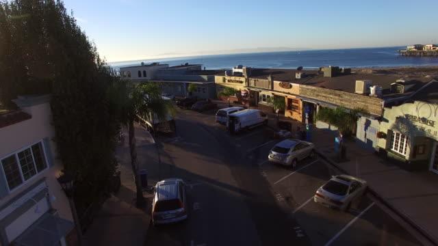 aerial shot of vehicles on street amidst buildings during sunset, drone ascending over coastal city against sky - santa cruz, california - santa cruz county california stock videos & royalty-free footage