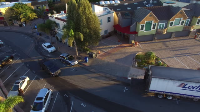 vidéos et rushes de aerial shot of vehicles on street amidst buildings in city, drone panning from right to left during sunset - santa cruz, california - quartier résidentiel