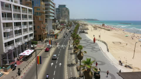 aerial shot of vehicles on street by buildings and beach in city, drone flying forward over promenade against sky on sunny day - tel aviv, israel - テルアビブ点の映像素材/bロール
