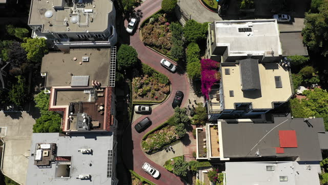 aerial shot of vehicles on zigzag street amidst buildings in city, drone ascending over cars on sunny day - san francisco, california - zigzag stock videos & royalty-free footage