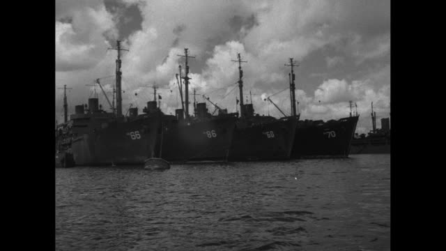 aerial shot of warships at pier / four shots of warships at anchor next to piers / shot of plane being lashed to deck of ship / shot of bulldozer... - bikini atoll stock videos and b-roll footage