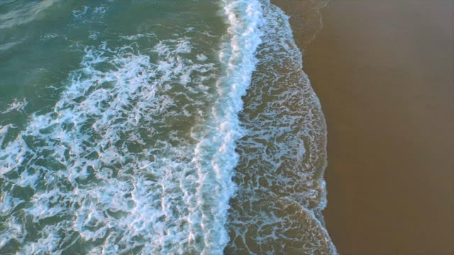 vídeos de stock, filmes e b-roll de aerial shot of waves breaking on the beach. - goodsportvideo