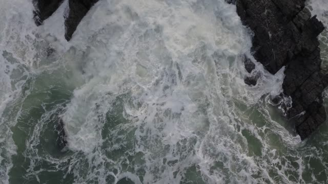 Aerial Shot of Waves Hitting Rocky Cliffs