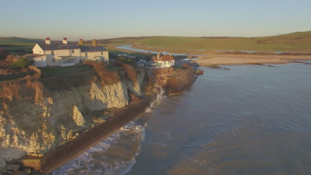 vídeos de stock, filmes e b-roll de aerial shot of waves hitting sea defences in front of cottages - erodido