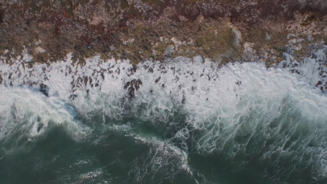 Aerial shot of waves on rocky coastline