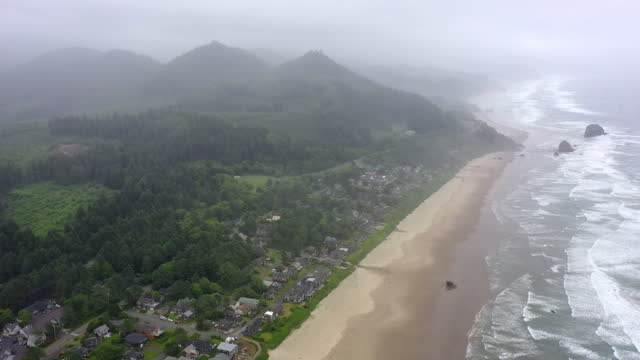 aerial shot of waves splashing at beach by city and mountains, drone flying forward over coastline against sky - cannon beach, oregon - oregon coast stock videos & royalty-free footage