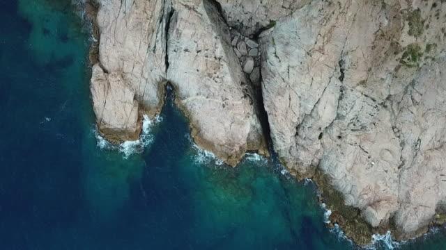 vidéos et rushes de aerial shot of waves splashing on rock formation in blue sea, drone ascending over ocean - tossa de mar, spain - mar