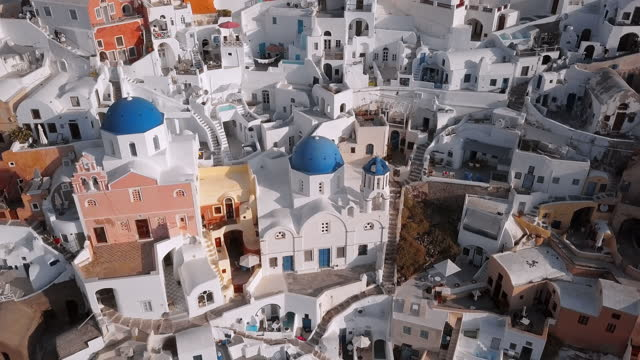 aerial shot of whitewashed structures in city on sunny day, drone flying over white houses - santorini, greece - cyclades islands stock videos & royalty-free footage