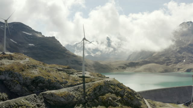 aerial shot of wind turbines on mountain by glacial lake, drone flying backward over landscape against sky on sunny day - swiss alps, switzerland - energieindustrie stock-videos und b-roll-filmmaterial