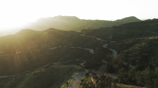 aerial shot of winding mountain road towards hollywood sign, drone flying forward towards famous landmark against sky at sunset - los angeles, california - mountain road stock videos & royalty-free footage