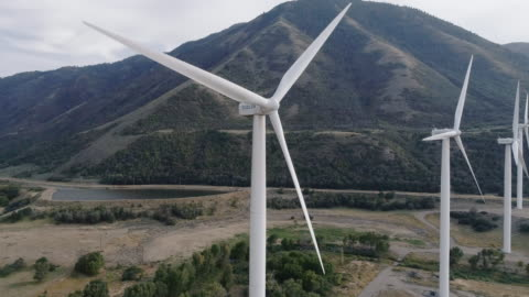 aerial shot of windmills spinning in a valley - wind turbine stock videos & royalty-free footage