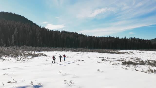 aerial shot of winter mountaineers walking across snowy valley - three people stock videos & royalty-free footage