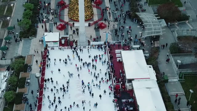 aerial shot of winter park people ice skating in the park at san francisco's union square and decorated christmas tree - winter点の映像素材/bロール