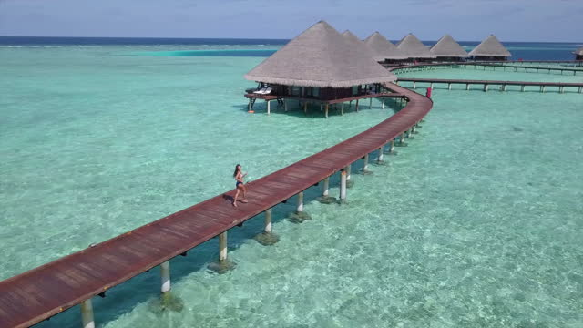 aerial shot of woman running on jetty amidst water bungalows, drone flying forward over turquoise sea at luxurious resort against sky - vaadhoo, maldives - urlaubsort stock-videos und b-roll-filmmaterial