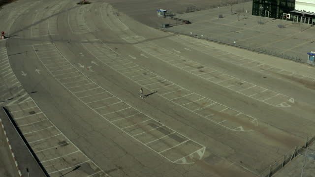 aerial shot of woman walking by markings in parking lot during pandemic, drone descending over cracked floor on sunny day - tel aviv, israel - moving down stock videos & royalty-free footage