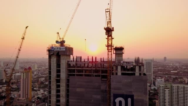 日没と作業建設現場の空中ショット - クレーン点の映像素材/bロール