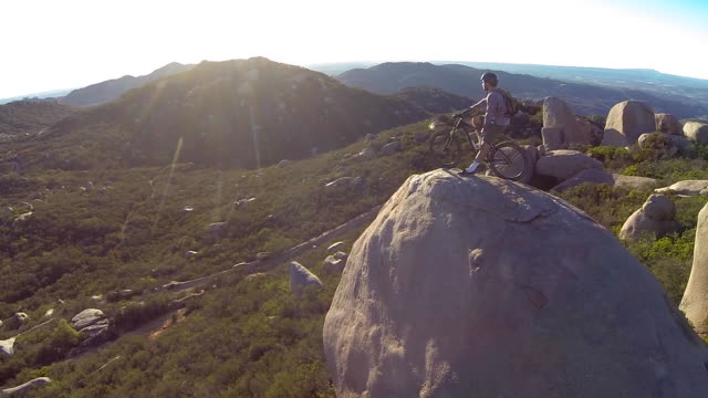 vídeos de stock, filmes e b-roll de aerial shot of young man mountain biker resting with his bike on a boulder. - grande angular